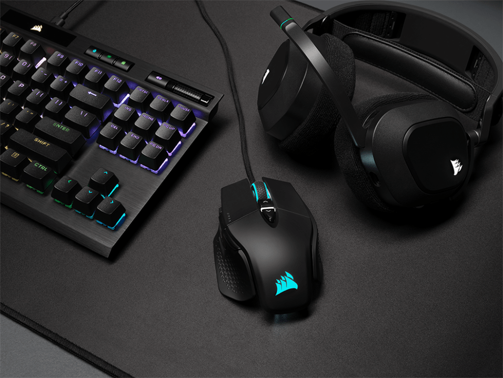 The M65 RGB Ultra gaming mouse on a desk with mousepad, K70 TKL gaming keyboard and HS80 RGB Wireless gaming headset
